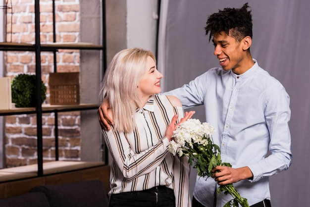 An african young man proposing her girlfriend by giving white flowers bouquet