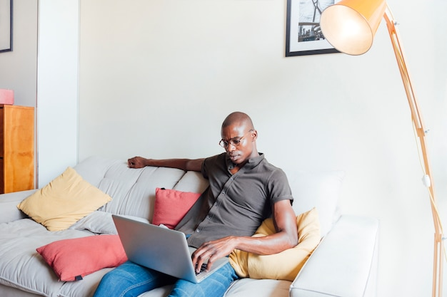 An african young man relaxing on sofa using laptop at home