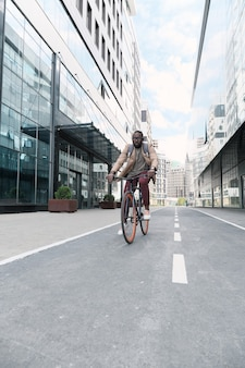 Африканский молодой человек катается на велосипеде по улицам города