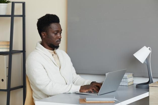 그는 사무실에서 노트북에 입력하는 그의 온라인 작업에 집중 테이블에 앉아 아프리카 젊은 남자