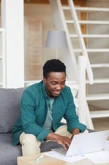Африканский молодой человек сидит на диване и печатает на портативном компьютере, он работает онлайн дома