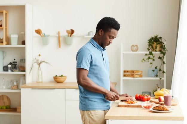 テーブルの近くに立って、自宅のキッチンで野菜を切るアフリカの若い男