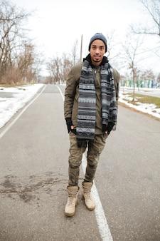 屋外の道に立っているアフリカの若い男