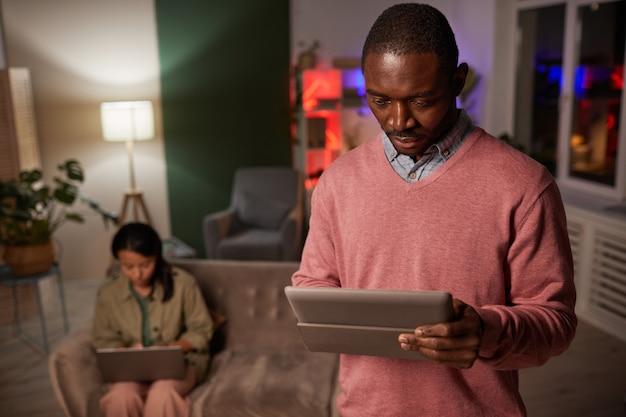 バックグラウンドで女性とオフィスに立っている間デジタルタブレットを使用してアフリカの若い男