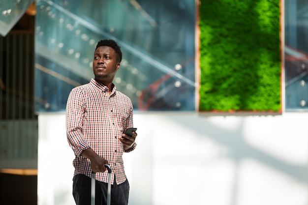 彼は飛行機で旅行している空港で荷物と携帯電話を持つアフリカの若い男