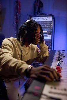 スタジオで曲を作曲するために音楽キーボードを使用してヘッドフォンでアフリカの若いミュージシャン