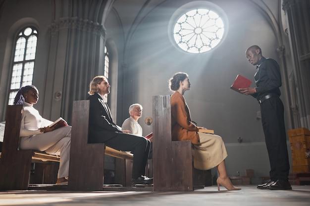 Молодой африканский священник читает библию для верных людей, сидя на скамейке в церкви