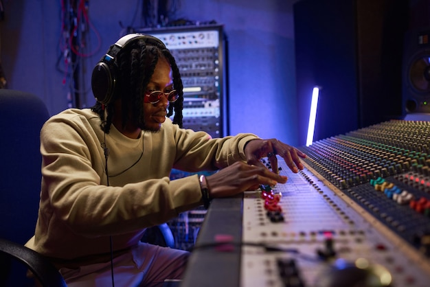 ミキシングミュージックボードで演奏するヘッドフォンのアフリカの若いプロデューサー、彼はスタジオで新しい曲を作成しています
