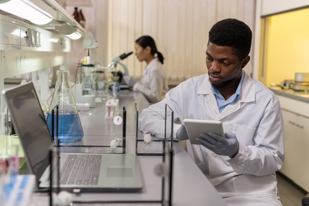 African young scientist using digital tablet and examining two types of mice in the boxes in the laboratory