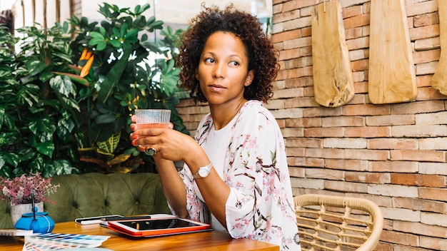 An african young woman drinking cocktail in the restaurant