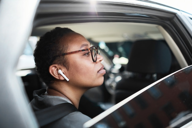 African young woman in eyeglasses and in wireless headphones looking through the window while sitting in the car