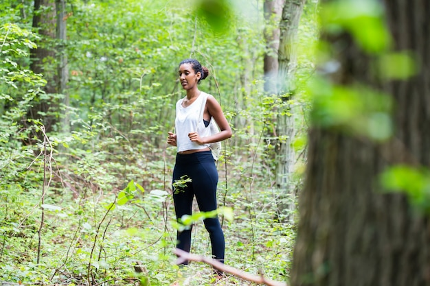 African young woman hiking on forest track