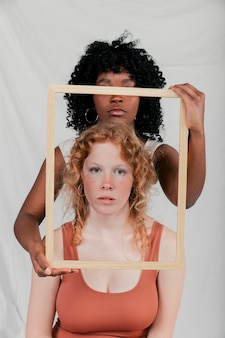 An african young woman holding wooden frame in front of caucasian female against grey backdrop