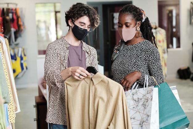 Африканская молодая женщина в маске покупает новую одежду с помощью продавца в магазине