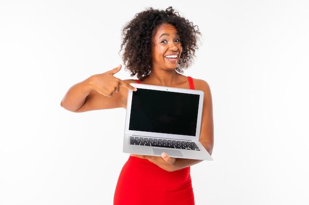 흰색 배경에 모형 이랑 노트북 화면을 보여주는 아프리카 젊은 여자