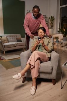 部屋で彼女の後ろに立っている男性と彼女の携帯電話で写真を見て肘掛け椅子に座っているアフリカの若い女性