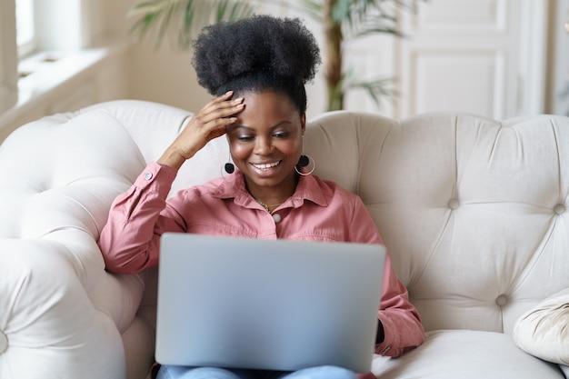 Африканская молодая женщина, сидящая на диване, разговаривает в онлайн-видеочате или веб-семинаре с друзьями дома.