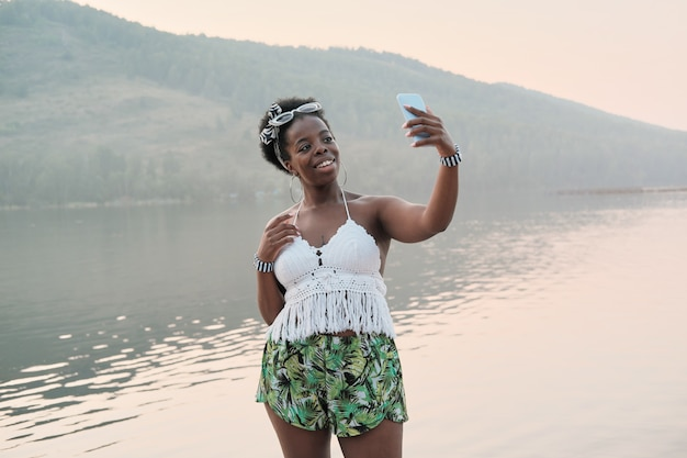 African young woman standing against the mountain and the lake and making selfie on her mobile phone