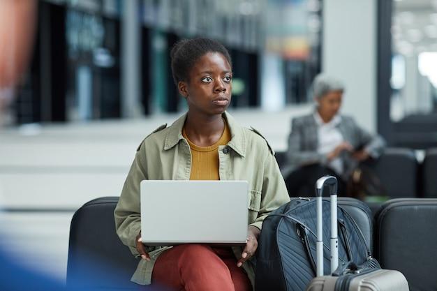 Африканская молодая женщина, использующая свой портативный компьютер, сидя и ожидая своего рейса в аэропорту