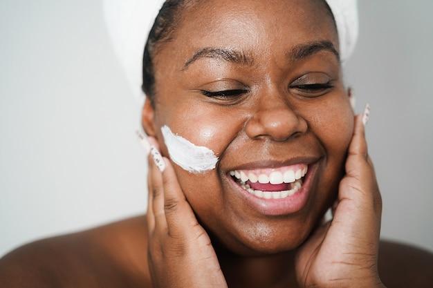 スキンマスクを身に着けているアフリカの若い女性-美容トリートメントとボディケアのコンセプト-左目に主な焦点