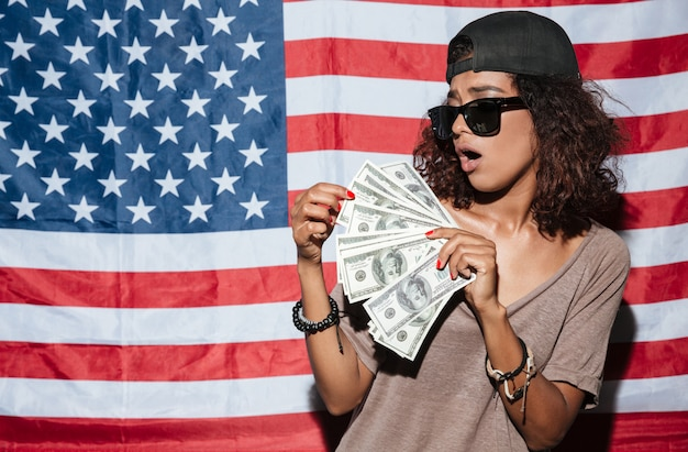 アメリカの国旗の上に立ってお金を持つアフリカの若い女性