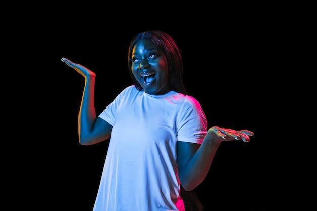 人間の感情の顔の表情の若者の販売広告のネオンの概念で暗い壁にアフリカの若い女性の肖像画