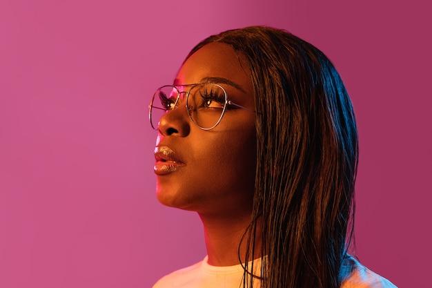 人間の感情の顔の表情の若者の販売広告のネオンの概念で壁にアフリカの若い女性の肖像画