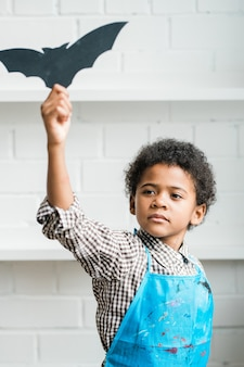 African youngster in blue apron holding handmade halloween symbol in shape of black bat in raised hand