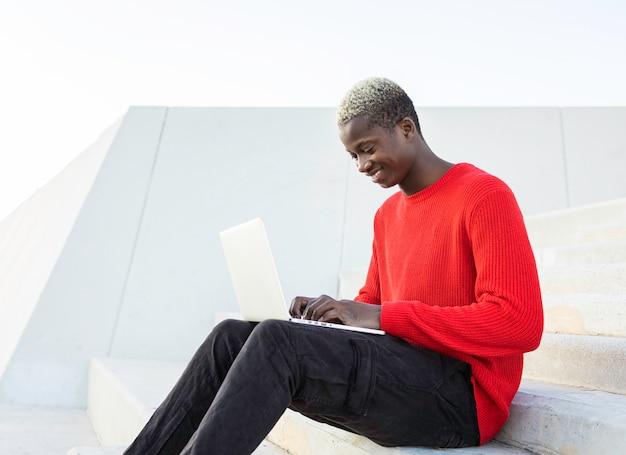 ラップトップコンピューターを持つアフリカの若者