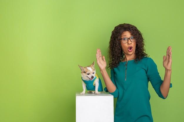 緑のスタジオの背景に小さな犬とアフリカ系アメリカ人の美しい若い女性の肖像画