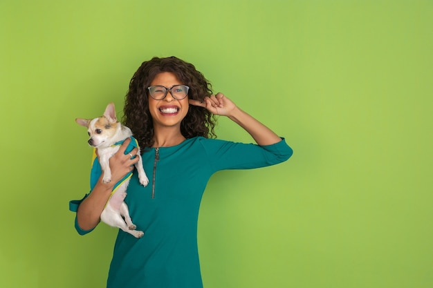 녹색 스튜디오 배경에 작은 강아지와 함께 아프리카 계 미국인 아름다운 젊은 여성의 초상화