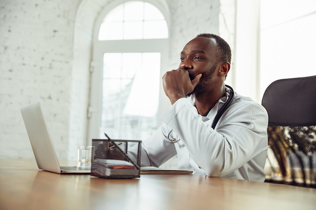 Афроамериканский врач консультирует пациента, работающего в кабинете крупным планом