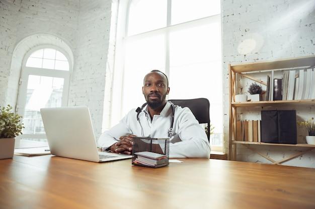 Афроамериканский врач консультирует пациента, работающего в кабинете