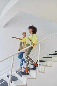 アフリカ系アメリカ人の洋裁師は、成熟した同僚が階段を下りる前に何かを指しています