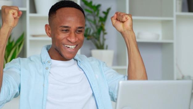 Афроамериканец счастлив, получив отличные новости из интернета, смотрит на экран компьютера, поднятые руки кричат от радости, празднуя победу в онлайн-лотерее