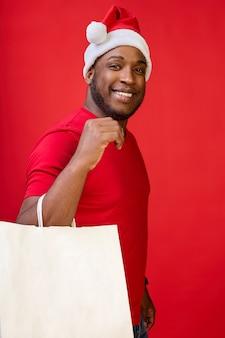 Афроамериканец-гей сладко улыбается в шляпе санты и держит в руках белые бумажные пакеты.