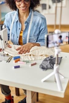 アフリカ系アメリカ人の女性デザイナーがスタジオのテーブルで機械撮影ビデオで縫う