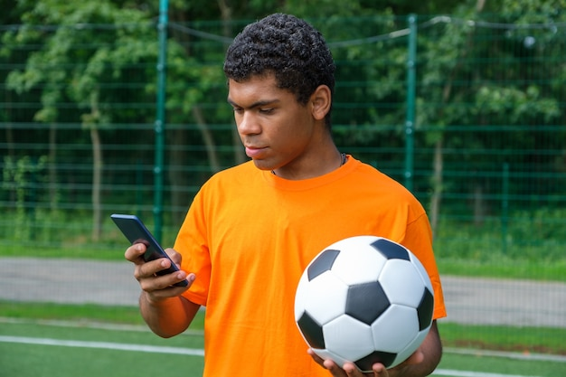 Africanamerican man holding soccer ball and use smartphone on sports court