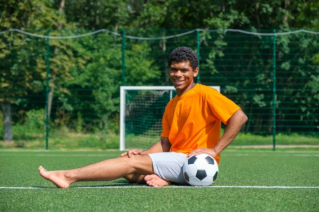 Africanamerican man holding soccer ball while sitting on sports court
