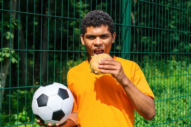 Афроамериканец держит футбольный мяч, стоя у забора