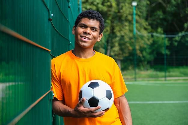 울타리에 서 있는 동안 축구공을 들고 아프리카계 미국인 남자