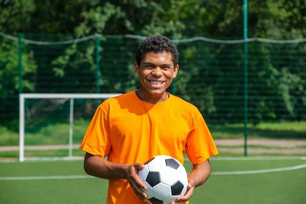Афроамериканец держит футбольный мяч, стоя на спортивной площадке