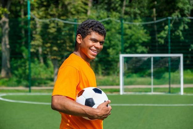 スポーツコートに立っている間サッカーボールを保持しているアフリカ系アメリカ人の男