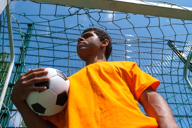 Africanamerican man holding soccer ball while standing in soccer goal