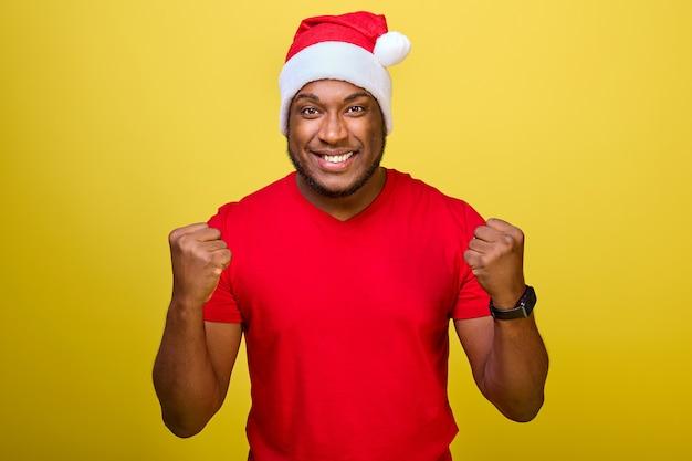 Афроамериканец в красной футболке и рождественской шляпе делает жест сжатыми кулаками