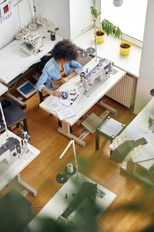 Афроамериканка-дизайнер смотрит на рисунок на швейной машине, снимая видео в студии
