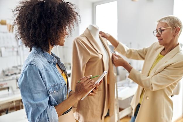 アフリカ系アメリカ人の女性がスケッチブックを描き、成熟した女性の仕立て屋がワークショップでジャケットを測定します
