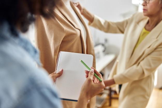 アフリカ系アメリカ人の女性は、成熟した女性の仕立て屋が働いている間、空白のスケッチブックと緑の鉛筆を持っています