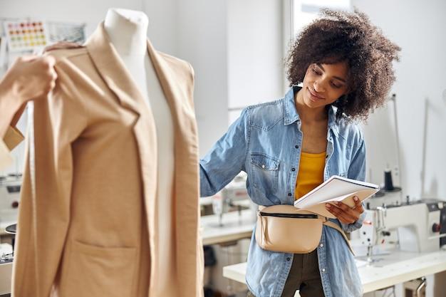 ノートブックを持つアフリカ系アメリカ人の女性は、デザイナーが詳細を測定しながらスタイリッシュなベージュのジャケットを見ています