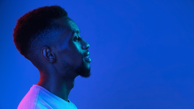 Africanamerican young mans portrait on dark studio wall in neon side view